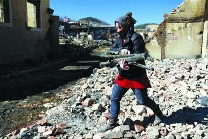 一位商户在自家店肆的废墟里清理出藏刀 /晨报特派记者 杨育才
