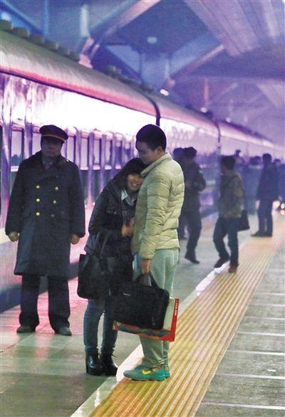 1月16日,北京站,开往重庆的临客列车外,一对情侣正在告别。新京报记者 王嘉宁 摄