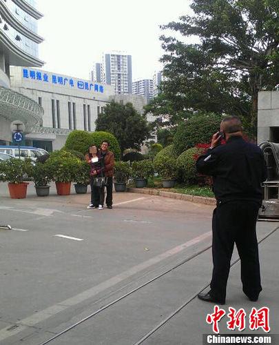 4月8日下午17时许,昆明市新闻中心门口发生劫持人质事件。图为劫持者与警方对峙。中新社发 杨晶 摄