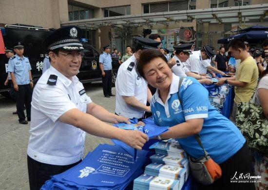 公安部副部长、北京市委常委、公安局长傅政华现场为大家发放反恐宣传品。人民网记者 张雨摄