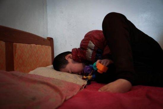2014年3月11日,山东临沂,李致康疲惫地蜷缩在床上,手里拿着他最喜欢的玩具,他每天几乎所有的时间都在这张床上渡过。澎湃新闻兰卉图