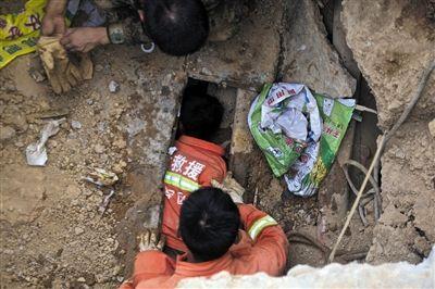 一名官兵欲将麻绳递给熊正芬系上,并将她抱出废墟。