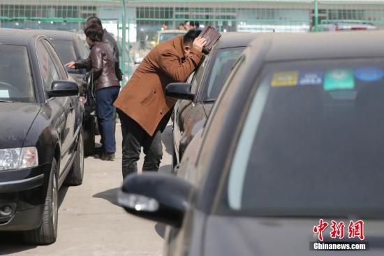 """3月15日,市民正在拍卖会预展上参观车辆。当日,第二轮""""中央和国家机关公车改革取消车辆""""在北京北汽鹏龙机动车拍卖有限公司进行预展。拍卖会将于3月18日和3月30日举行。中新社发 熊然 摄"""