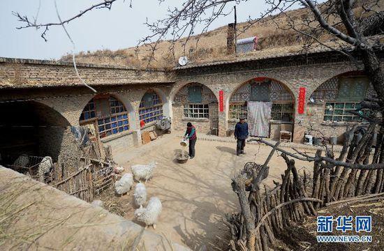 新华社照片,横山(陕西),2015年3月17日 两个人的村庄 王明厚(右)和高生花在院子里给羊喂水(3月16日摄)。