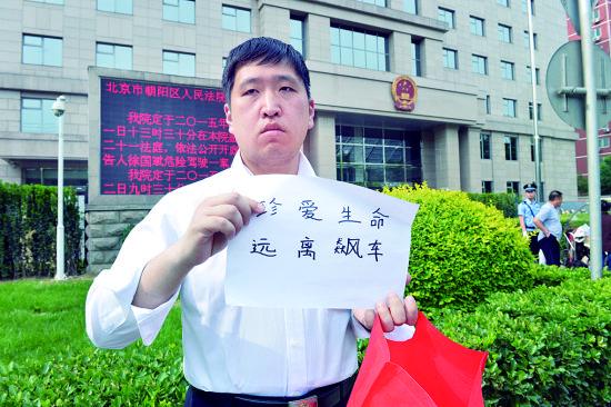 """上午,一名市民来到旭日法院门前举着""""珍视性命,阔别飙车""""的口号 摄/记者刘畅"""