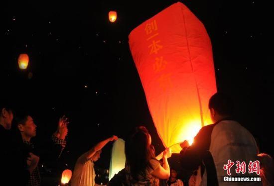 6月4日,赶考前夜,高三学生与陪读家长在学校周边的空地上放飞孔明灯,预祝高考金榜题名。 中新社发 韩苏原 摄
