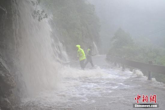 浙江省桐庐县富春江镇芦茨村白云源景区附近,部分道路因山体滑坡造成塌方,车辆不能进出。而后,相关部门工作人员在风雨中抢修,终于恢复通行。 吴新宇 摄