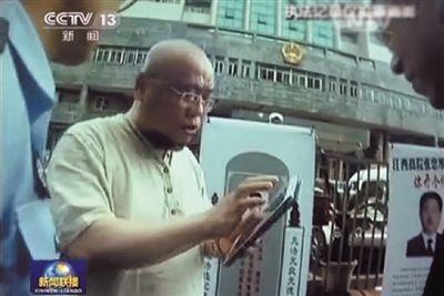 """吴淦网名""""超级低俗屠夫"""",他通常负责去案件审理地制造影响给法院施压。央视截屏"""