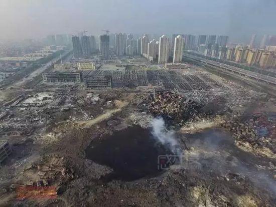 """▲ 8月15日上午,天津滨海化学品爆炸现场烟雾逐步散去,爆炸""""原点""""现出一个巨大的坑,坑内有大量液体,深度未明。张志韬 摄"""