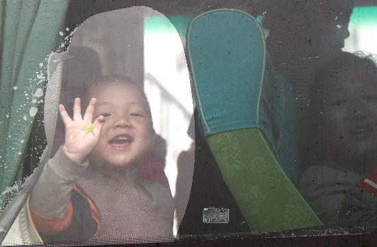 图文:一位返乡的小朋友正向送别的人群挥手告别