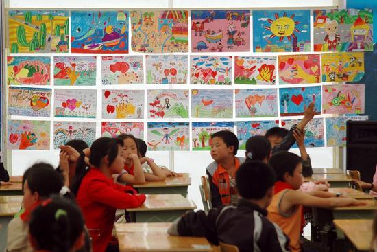 图文:帐篷教室的墙上挂着孩子们画的画