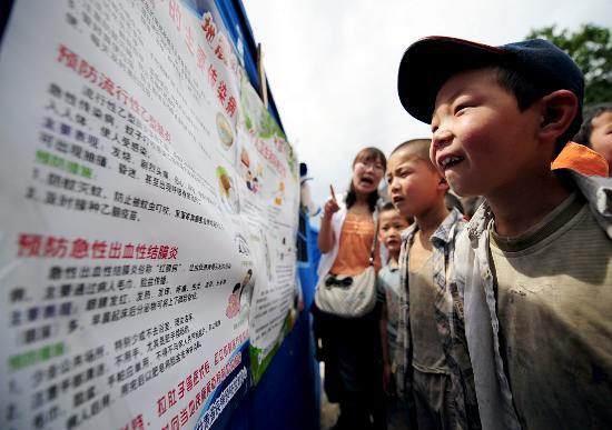图文:灾区学生正在看疾病防疫宣传展板