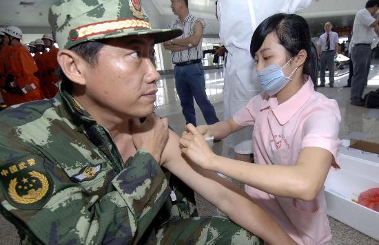 图文:护士为海南救援队的工作人员注射防疫针