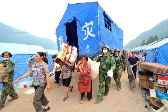 图文:战士将灾民的帐篷抬到新平整的场地上