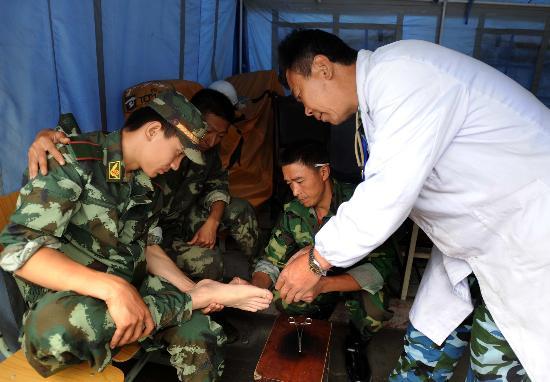 图文:志愿者在帐篷诊所里为一位受伤士兵治疗