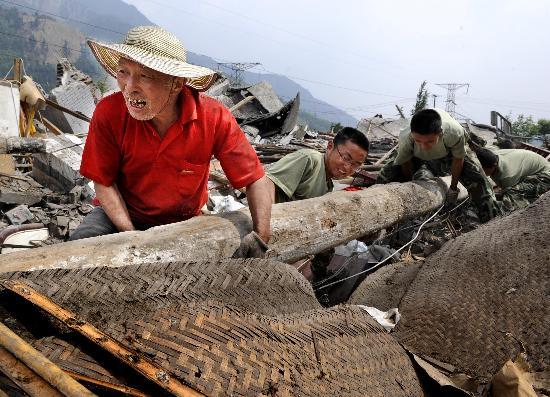 图文:村民马富阳在武警官兵帮助下清理废墟