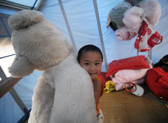 图文:3岁孤儿林帝丞在玩志愿者送来的玩偶