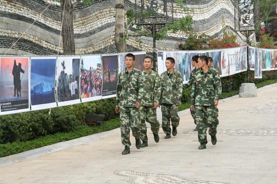 图文:几个穿迷彩服的军人观看作品