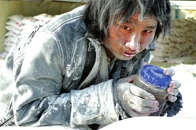 一名工人抱着水杯在成品大白粉堆上发呆。《新疆都市报》供图