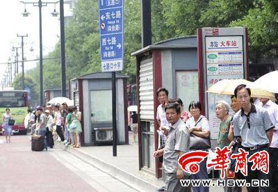 西安火车站前的解放路上,人们在公交车站牌旁等车 本报记者 汤继颖