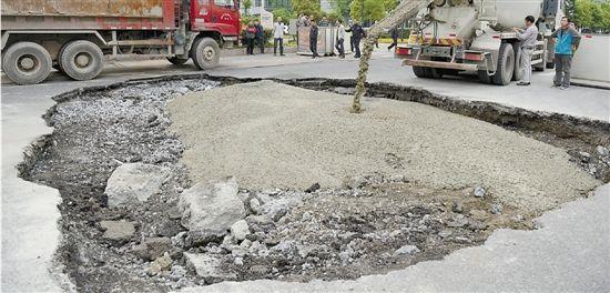 路面大坑回填中。 本报记者 董旭明 摄