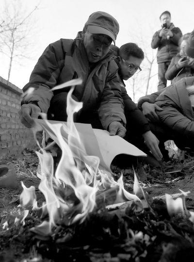 李三仁在儿子坟前燃烧再审无罪裁决文书的复印件。新华社发