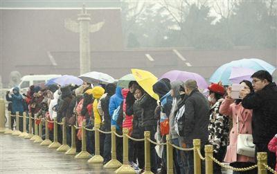 昨日,游客在北京天安门广场撑伞等待观看降旗仪式。当日下午北京普降小雪。新华社发