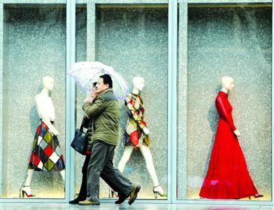 昨天,阴雨潜入上海。淮海路环贸iapm商场前,路人打起雨伞赶路。/晨报记者 殷立勤