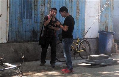 """6月20日,平安里育德胡同,男子(左)正给家里打电话让汇钱,""""医托""""守在其旁边。"""