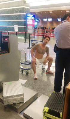 """男子因为无法登机,气急败坏将柜台多项用品扫在地面上,男子甚至裸上身坐在行李磅秤上,露出身上的刺青,引起旅客侧目。台湾""""中央社""""图"""