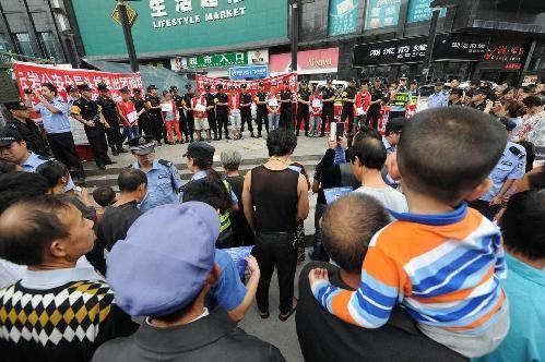 身着鲜白色囚服、拖着惨重的脚镣,7名盗抢嫌犯日前在特警的押送下,到贵阳闹市指认现场,诱发大众围观。