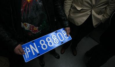 2013年3月25日,上海某二手车交易中心内,一车主展示新购买的二手车牌。