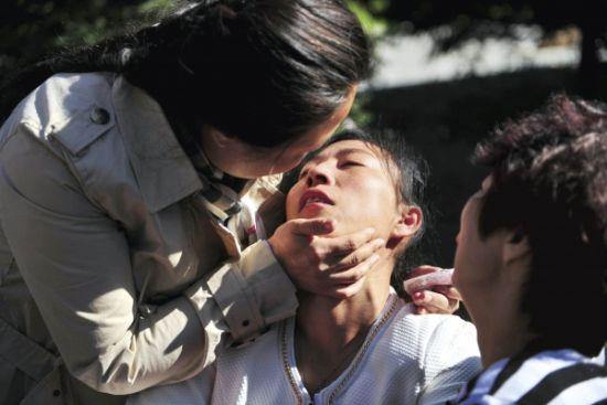9月26日,张晶(中)在领取到丈夫的骨灰后放声大哭,几近昏厥