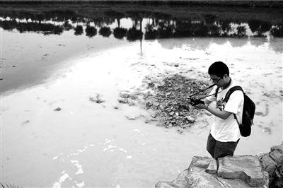 6月20日,在凉水河河道污染处,志愿者在拍照。(资料图片)本报记者朱嘉磊摄