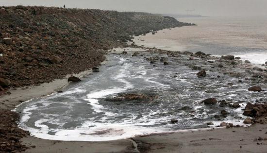 钱塘江畔污水形成巨大的漩涡,墨黑色、泡沫状的工业废水和潮水颜色差异非常明显,呈漩涡式向周围迅速扩散,黑色污染带绵延数公里。