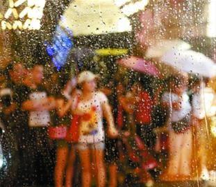 久违的雨水带来少许清凉,路人在南京路商店门口躲雨。