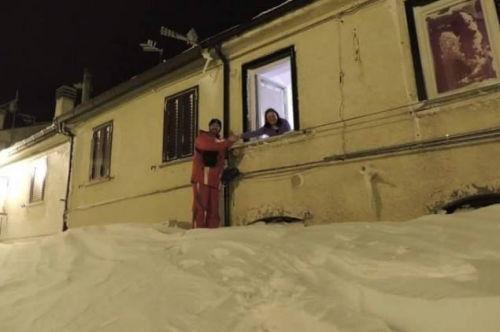 一个居民站在积雪上,可以与一名二楼邻居在窗口握手。(来源:意大利气象局)