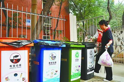 甸柳小区居民向分类收集垃圾桶内倒垃圾.
