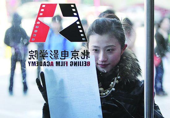 2月8日,一名报考北京电影学院表演学院的学生在查看报名信息。当日,北京电影学院招生工作正式开始。2012年本科计划招生455名(无分省计划),有9个院系的23个专业方向招生。 新华社发(李方宇/摄)