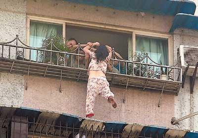 女子疑有精神病身体悬挂在窗户护栏