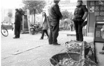 2月18日中午,天力批发市场前仍有小摊贩在此售卖水果。看来,要妥善解决这一带的乱象,当地管理部门还应深思。左图为网上疯传的视频图。记者 徐德荣 摄