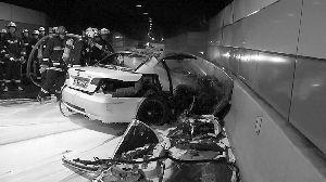 昨天上午,消防员正在外滩隧道内扑救撞击后燃烧的宝马车。
