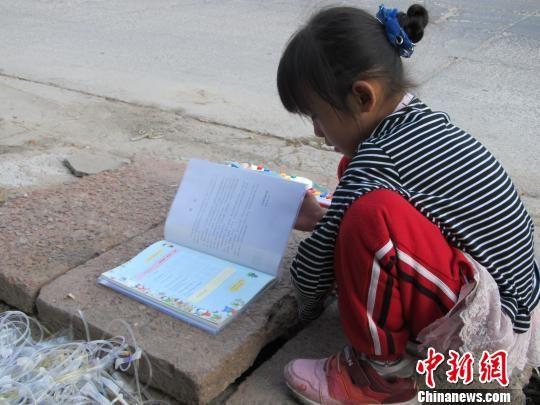 马江的小孙女正在院子里的一块石板上看书。 宋锦丰 摄