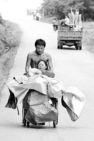 樊蒙推着母亲行走在213国道普洱至西双版纳段。