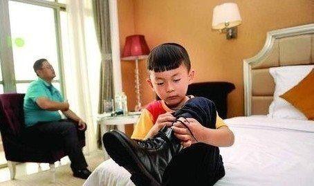 """10月7日,长沙星沙一家酒店,5岁的小男孩多多在一旁独自脱靴子,何烈胜的""""鹰式教育""""是为了锻炼孩子的身体和品格。 图/记者杨旭"""