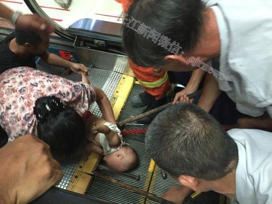 男童的手被卷进电梯,消防人员在全力施救。