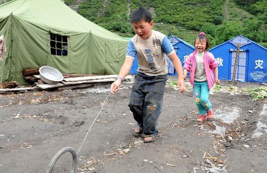 图文:理县两个孩子在帐篷前推轮胎玩耍