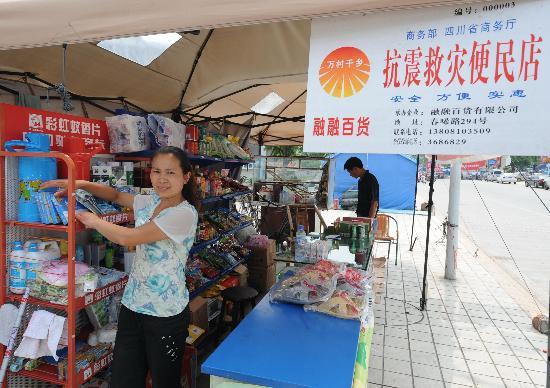 图文:一名妇女在抗震救灾便民店整理货物