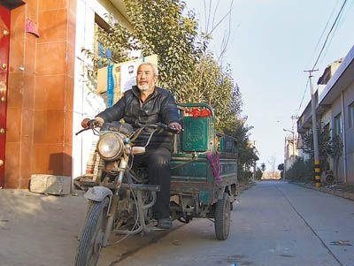 何智民每次都騎著這輛沒有頂棚的三輪摩托車去找兒子。在他身後的硬紙板上,貼著尋人啟事。付雁南 攝