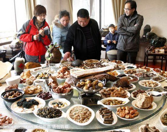 """石头宴""""大厨""""伍士军(右二)向游客介绍石头""""烹制""""的美食"""